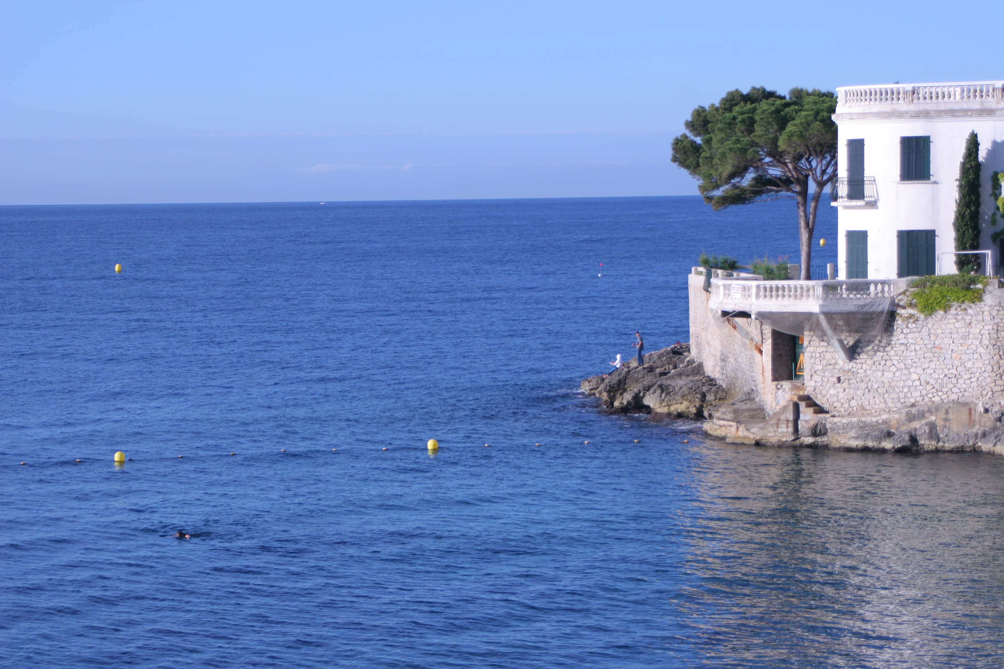 A morning swimmer crosses the harbor while a boy fishes on the rocks below a seaside villa. Cassis, France.